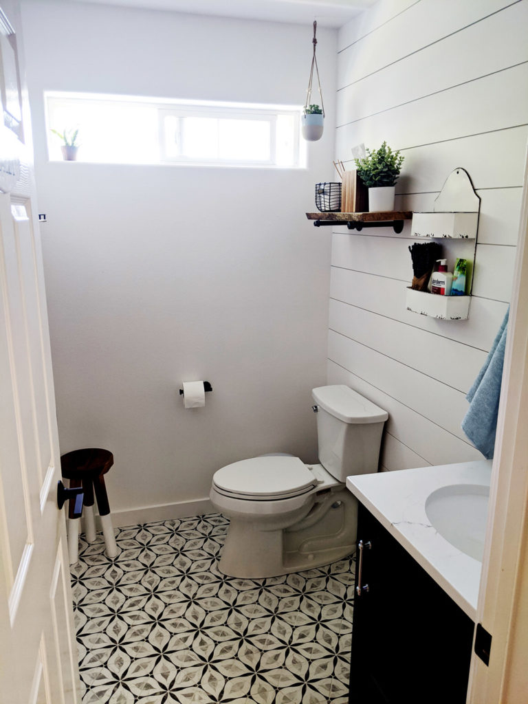 freshly remodeled bathroom with a black and white high-contrast tile floor and coped and painted shiplap on the walls.